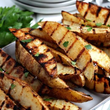 Angled stack of grilled potato wedges on a rectangular plate.