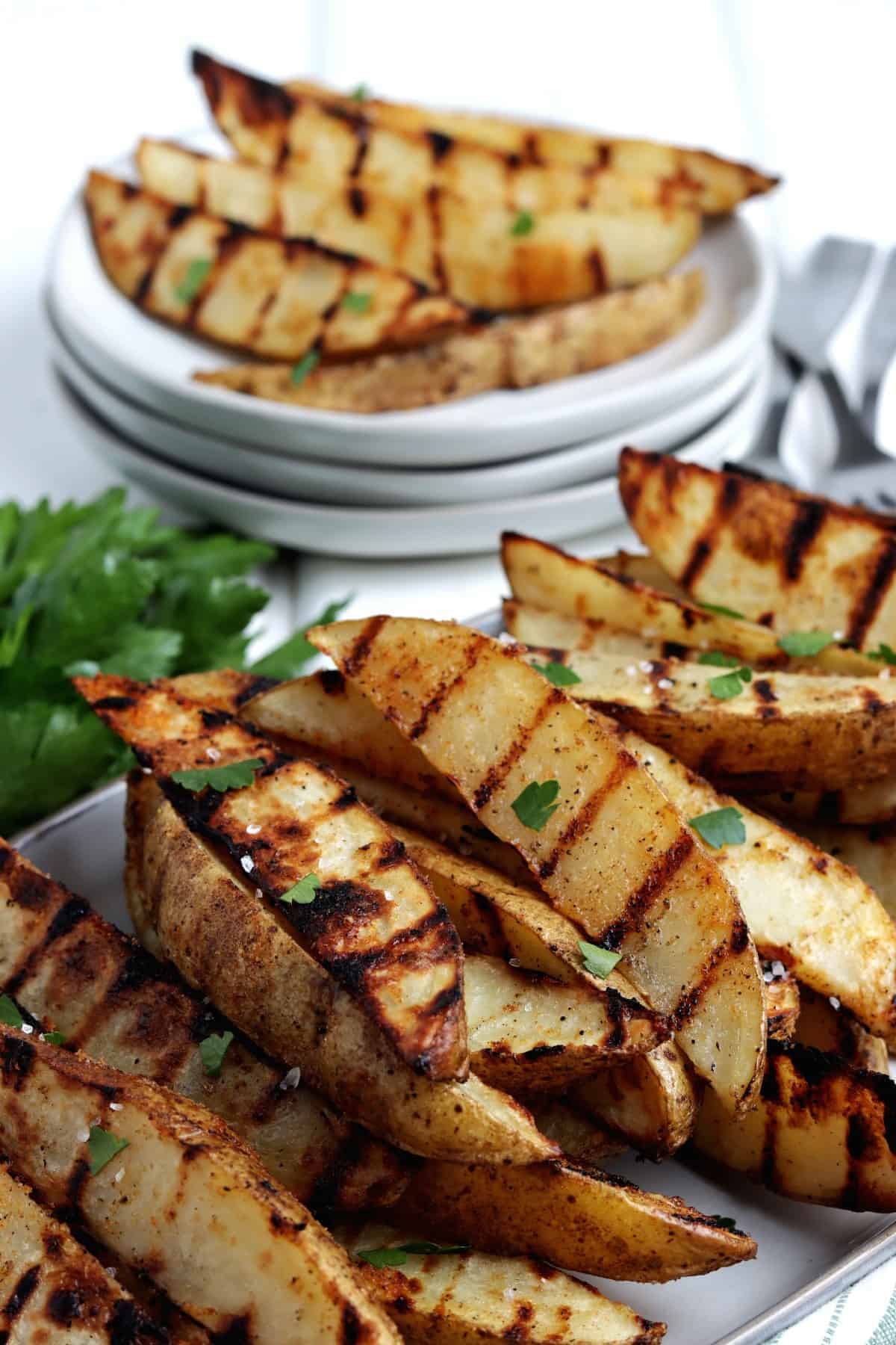 Close up angled photo of golden brown veggies stacked with small plates behind,