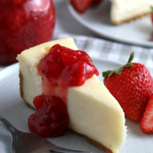 Slice of cheesecake with strawberry sauce poured over the top.