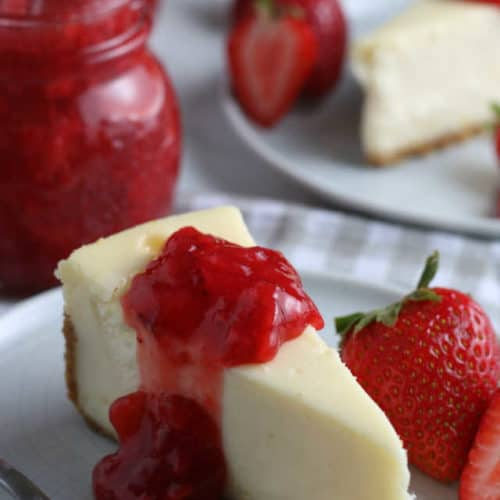 Slice of cheesecake topped with a strawberry topping.