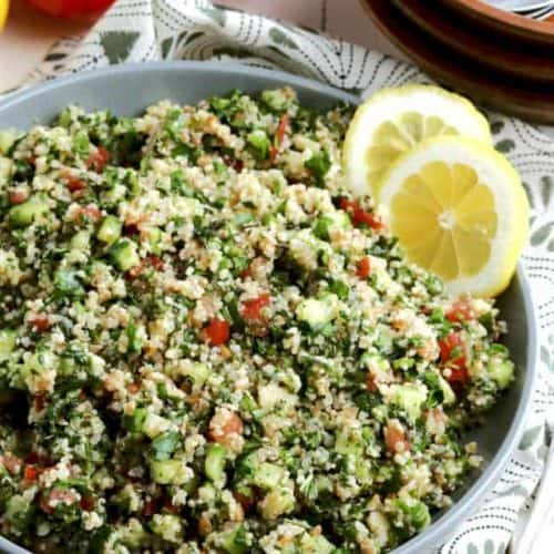 large bowl full of tossed tabouli salad with grains.