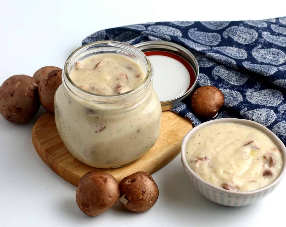 A jar and bowl filled with homemade vegan cream of mushroom soup.