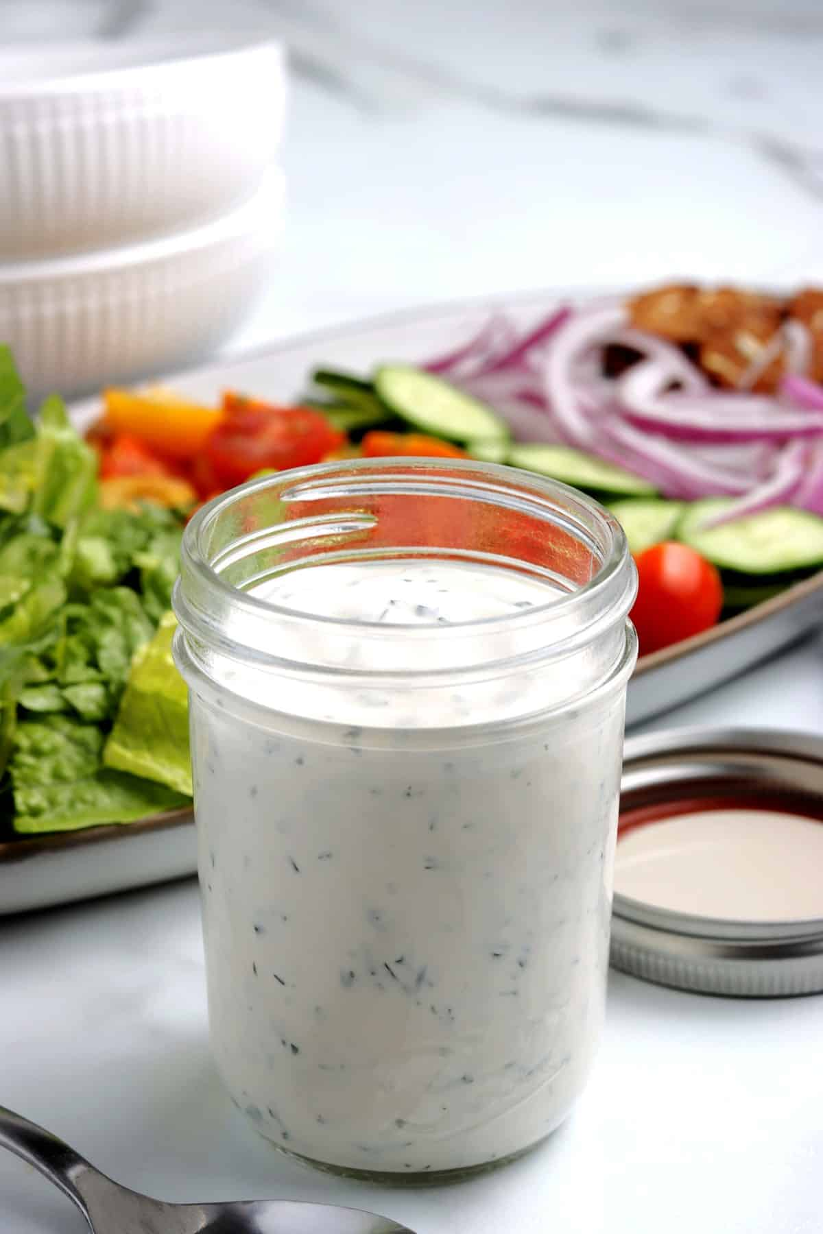 A small jar full of a creamy condiment for fresh salads.