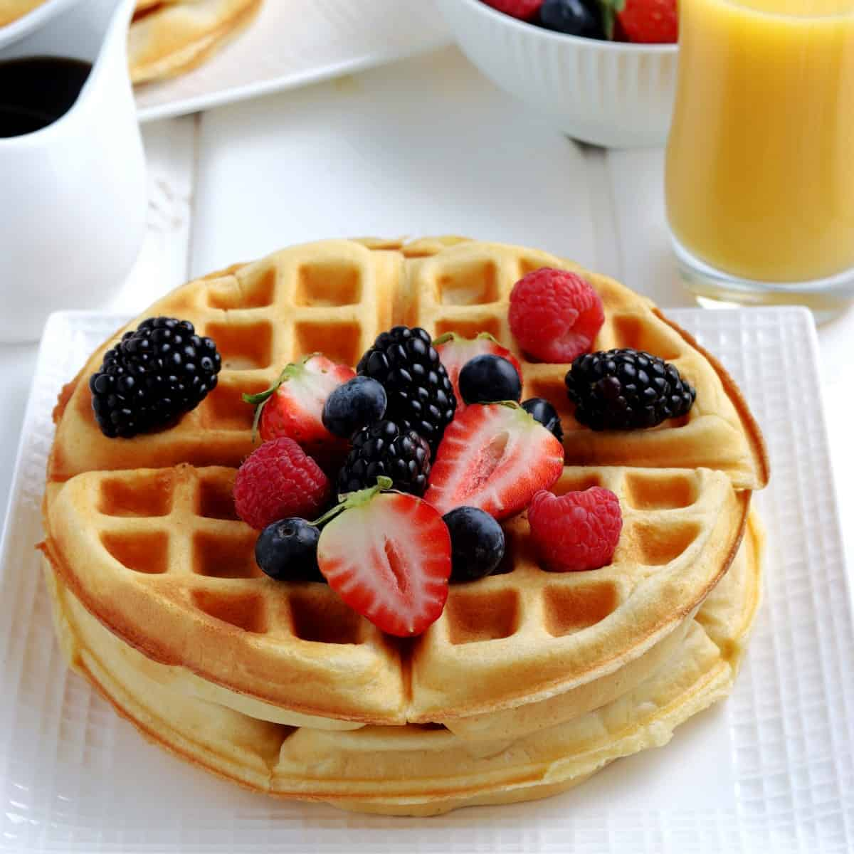 Two breakfast treats on a plate with fresh berries on top.