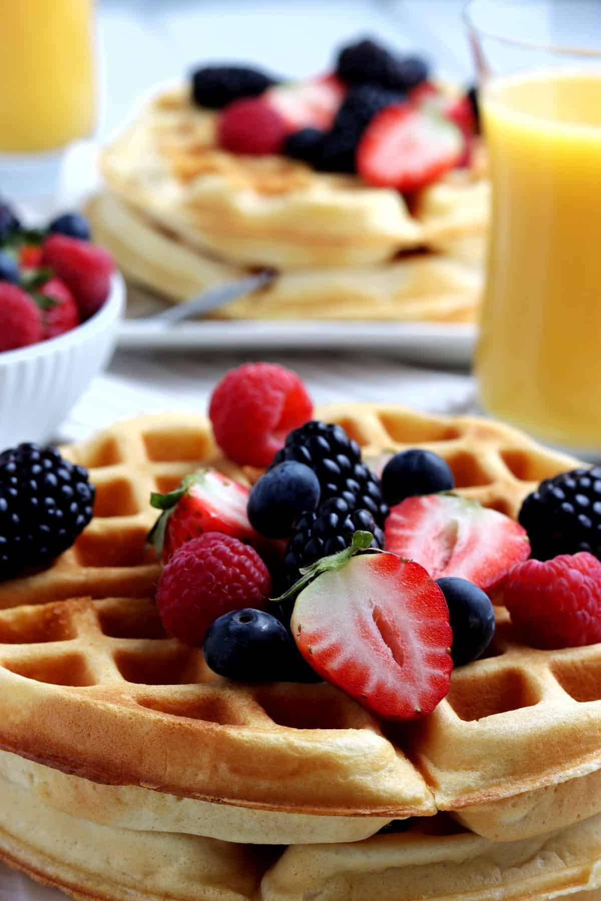 Close up of breakfast with berries and orange juice behind.