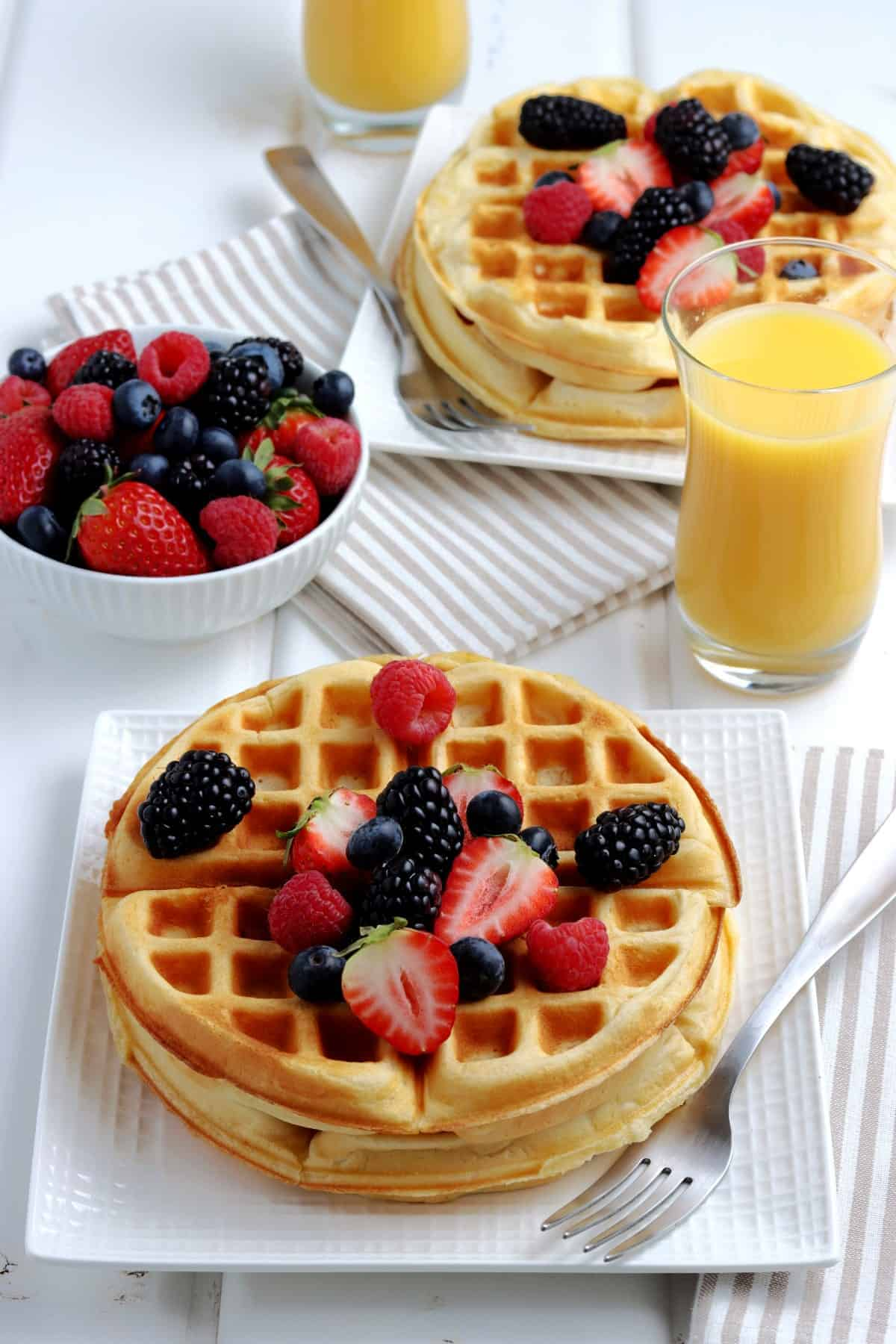 Full setting at the table with homemade waffles recipe, oj, berries and syrup.