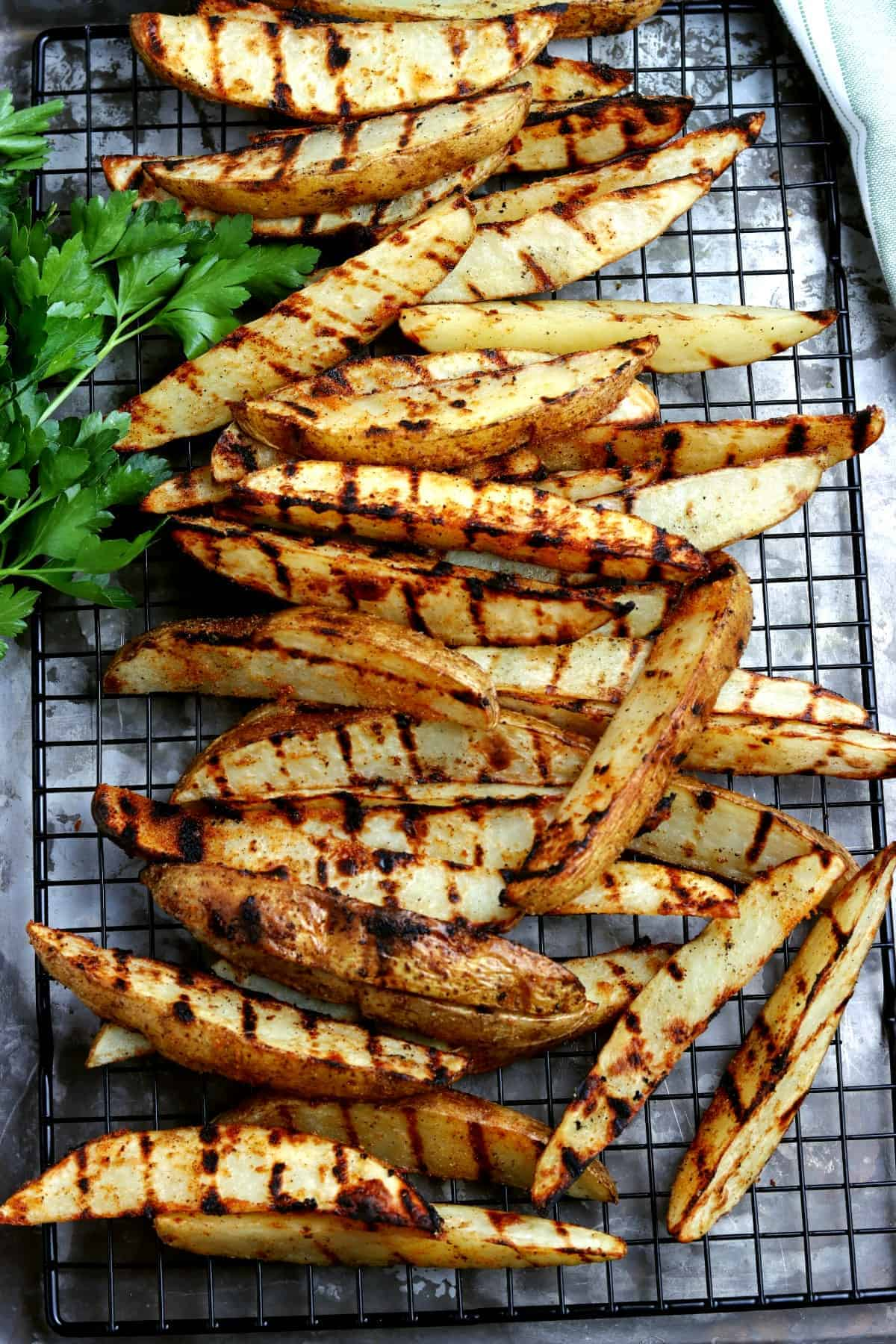 Overhead view of grilled potato wedges side dish on a rack.