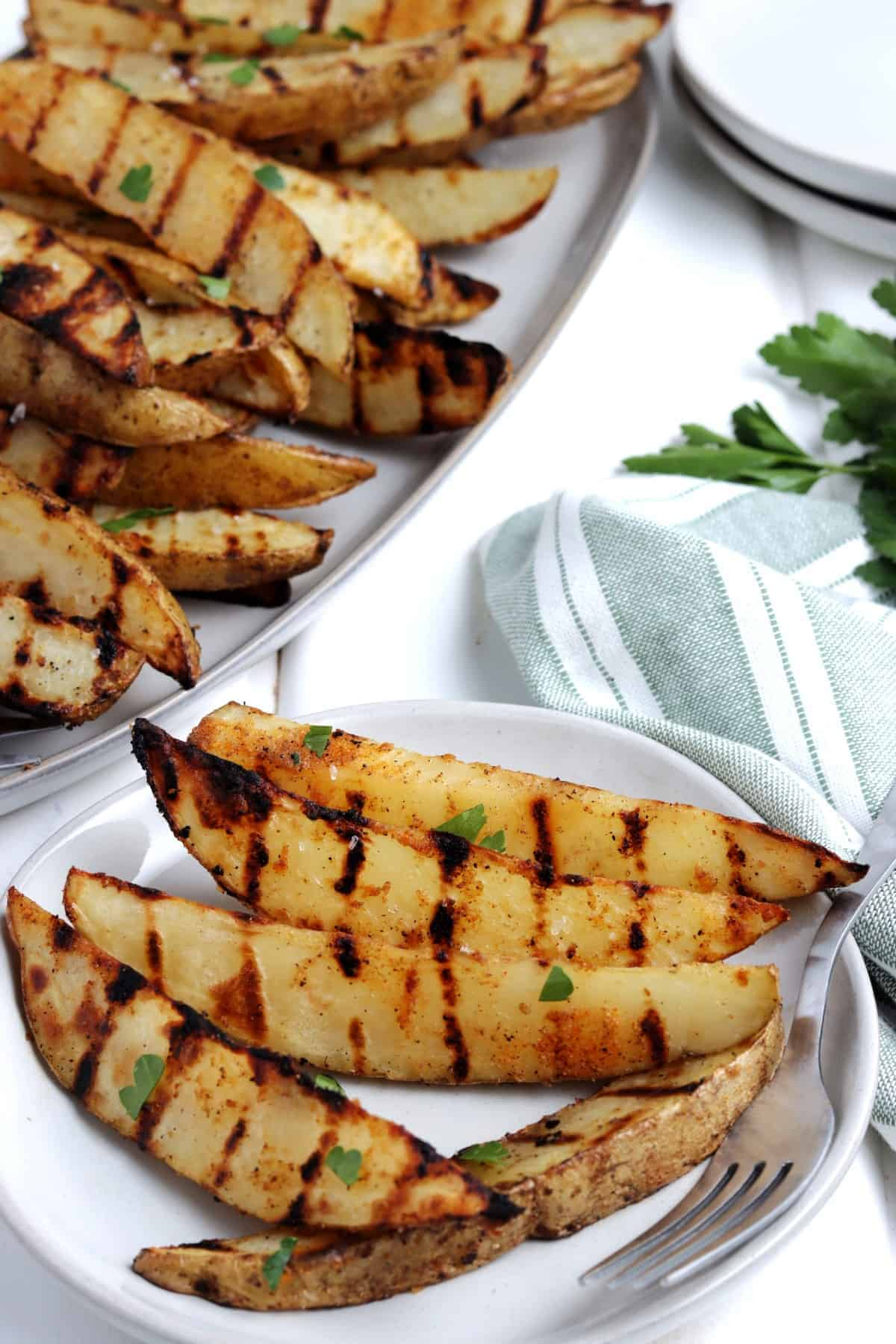 A nice serving of grilled veggies on a small plate with more behind.