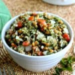 Titled bowl filled with tabouli salad on a beaded mat.