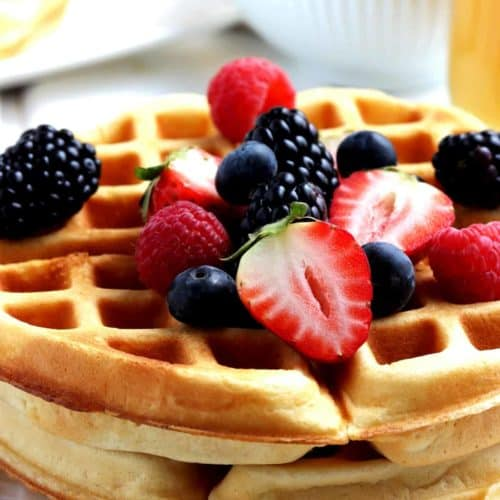Close up of stacked waffles with fresh fruit on top.
