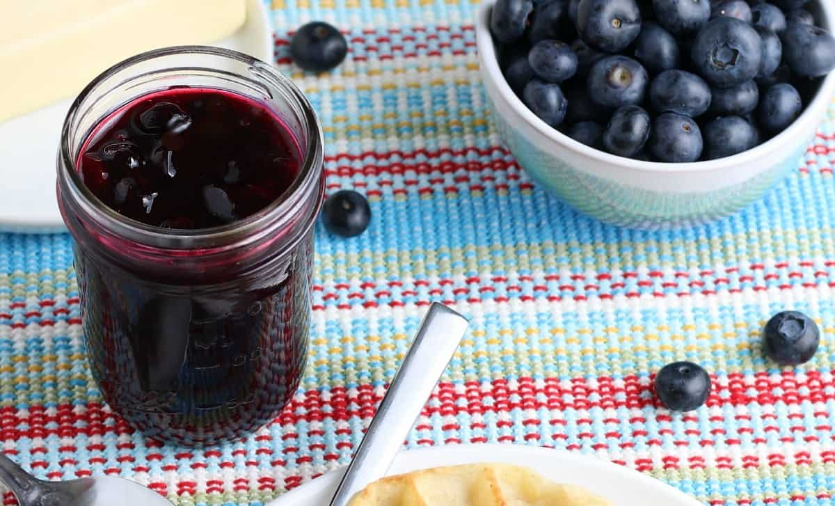 Wide photo of a jar full a complete blueberry sauce recipe.