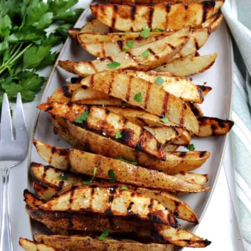 Overhead view of potato wedges in an oval platter.