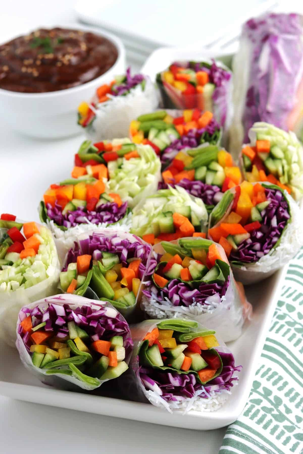 Platter of Vietnamese summer rolls and a bowl full of peanut dipping sauce.