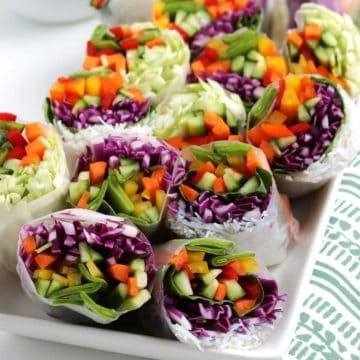 Close photo of sliced halves of summer rolls with lots of veggies.